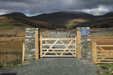 hardcore: A wooden gate leads to a causeway with a hardcore path flanked by metal fencing with cloud covered mountains in the distance  Stock Photo