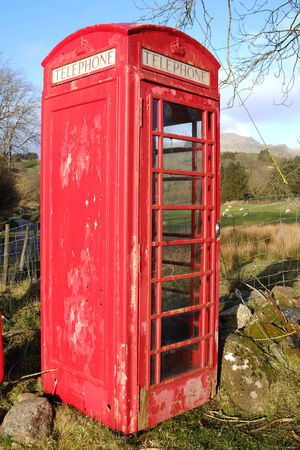 flaking: A vintage red British telephone box with flaking paint and