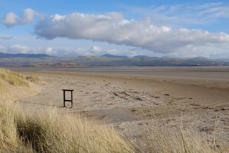 Sand dune grasses lead to a large deserted beach with empty sign post, a mountain range can be seen in the distance  Stock Photo