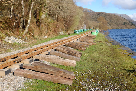 A railway line with old wooden sleepers laying along the track, bags of aggregate are lined up in the distance. Stock Photo