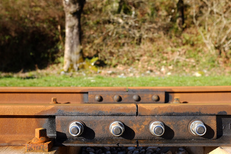A renewed joint on a railway line, line ends crossed with a metal bracket and new nuts and bolts. Stock Photo - 27537167