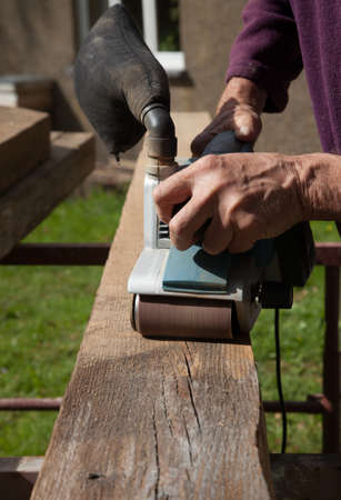 sander: A length of wood being sanded by a power sander held in strong hands. Stock Photo