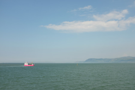 straits: A mussel fishing boat heading to port on the Menai Straits, Wales, UK, on the 0107 2014.