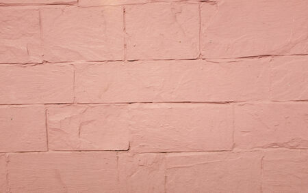 A pink painted rendered wall with embedded lines.