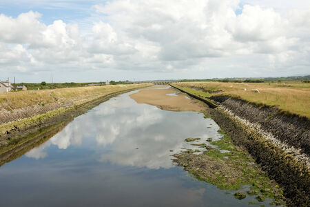 A constructed tidal river with high grass banks leads through marshland to the horizon with a cloudy sky.