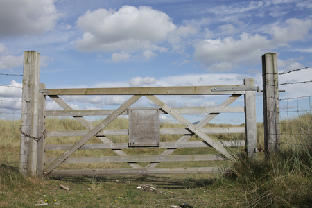 A closed wooden gate with a blank wooden sign against a grass landscape and blue sky with cloud. photo