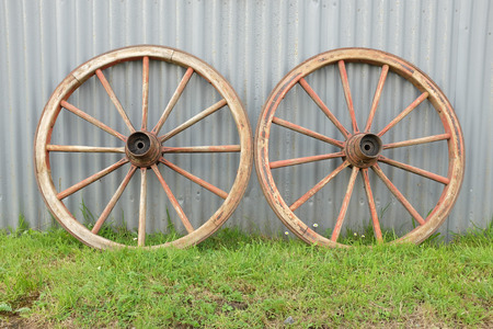 Green grass leads towards a pair of wooden made antique cart wheels resting against a metal wall. Stock Photo - 30842306