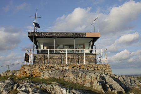 coastguard: A disused coastguard station on rocks with large windows and safety rail.