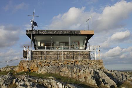 disused: Una estaci�n de guardacostas en desuso en las rocas con grandes ventanas y barandilla de seguridad.