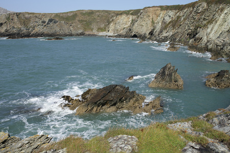 bosom: A view from a cliff top across the sea with rocks to cliffs enclosing Abrahams bosom bay, wales coast path, anglesey, Wales, UK. Stock Photo