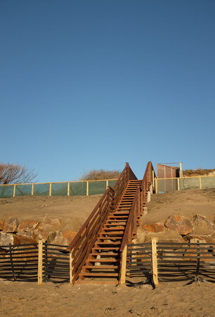 A set of wooden stairs, steps, built over a constructed dune with sand drift fence, base rock and overlayed sand.