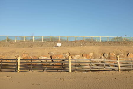 An area of constructed sand dune with a sand drift fence on wooden posts in front of a row of large rocks banked up with sand, a danger sign and a protective fence on top.