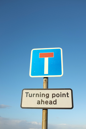 A dead end sign on a pole with a turning point sign underneath against a blue sky. photo