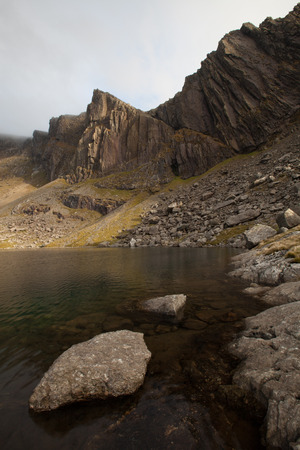 the crags: A rocky shoreline foreground leads passed a lake to the impressive mountain crags of Clogwyn Dur Arddu, Snowdonia national park, Wales, UK. Stock Photo