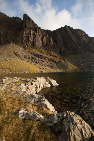 the crags: A rocky foreground leads to a lake and the impressive mountain crags of Clogwyn Dur Arddu, Snowdonia national park, Wales, UK.