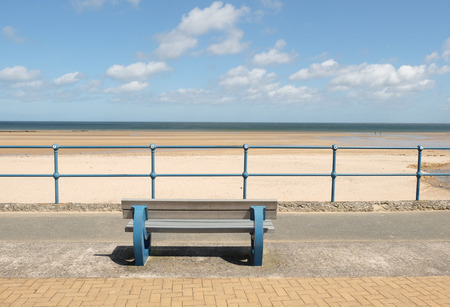 A blue painted bench and blue railings with a view across a deserted sand beach with the sea and blue cloudy sky in the distance.