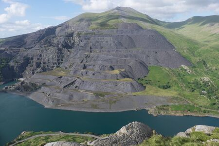flank: A view looking down to Llyn Peris and the expance of the Dinorwic slate quarry workings on the flank of the mountain Elidir Fawr, Llanberis, Gwynedd, Wales, UK. Stock Photo