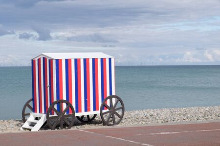 shingle: Victorian style bathing machine in red, white and blue stripes on a shingle beach with the sea in the background.