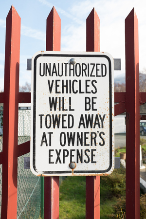 unauthorized: UNAUTHORIZED VEHICLES WILL BE TOWED AWAY AT OWNERS EXPENCE sign.