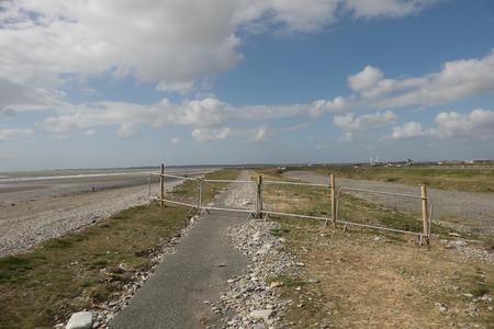 A temporary metal barrier closes off a tarmac footpath next to a beach.