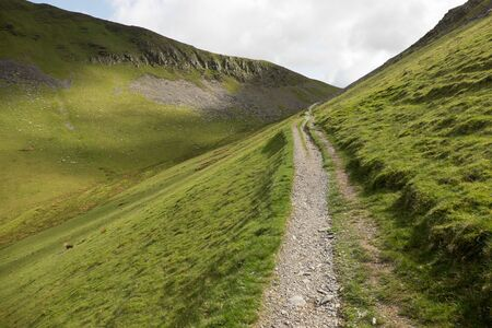 A footpath, track, leads up through steep grassy banks to a col on the horizon. Stock Photo