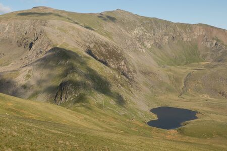 A view down grassy banks to Llyn Ffynnon y-gwas, a lake below the steep flanks of the west face of Snowdon, Wales, UK.