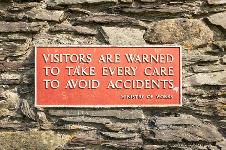 A vintage metal Ministry of Works sign, plaque, fixed to a stone wall, warning visitors to avoid accidents.