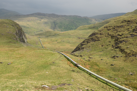 An over-ground pipeline stretches across moorland between hills.