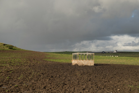 A metal feeder, hay hopper, in a field with grass and mud under a grey cloudy sky.
