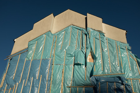 A gabble end wall with temporary plastic sheeting fixed with sections of wood.