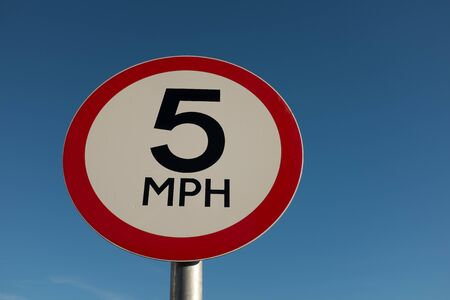 A circular road traffic sign with  5 MPH on a white background with a red border against a blue sky.