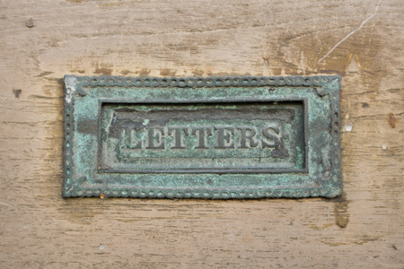 An old brass letterbox, tarnished green with the word LETTERS written on the flap with a patterned surround on a wooden background. Stock Photo