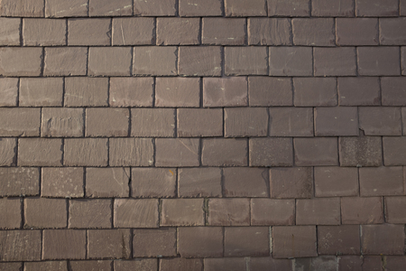 An old slate wall with a regular, alternate patterned design.