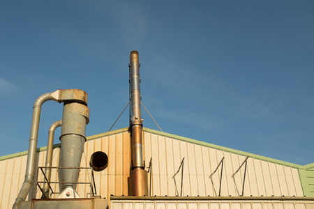 An industrial unit with a pipework system and metal exhaust stack against a blue sky. Stock Photo