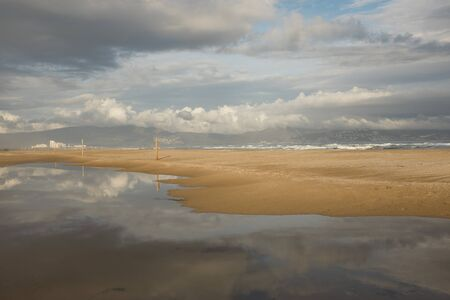 A moody sky is reflected in a pool of water and separated by a beach from the sea with cloud covered hills with buildings in the distance.