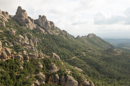 A track leads through trees under a rock tower ridge on the Mont Serrat complex, Catalonia, Spain, Europe.