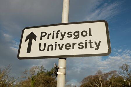 A bilingual EnglishWelsh directional University sign against a blue sky with cloud.