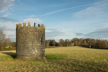 A stone built tower in a grass field leading to trees against a blue cloud sky. Stock Photo