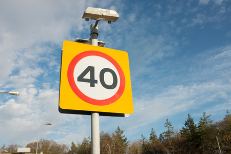 A road traffic sign with 40 in a red circle against a yellow background with a blue cloudy sky in the distance. Stock Photo