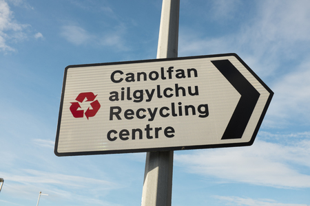 A directional  biligual English  Welsh recycling centre sign with red recycle symbol against a blue sky with cloud.