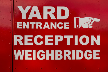 A red painted background with the words  YARD entrance reception weighbridge painted in white and a hand direction indicator.