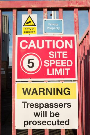 A variety of warning signs grouped on metal railings.