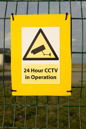 A yellow backed sign with the CCTV warning symbol and the words 24 Hour CCTV in Operation fixed to a green metal fence.