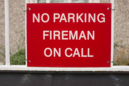 A red sign attached to railings with the words NO PARKING FIREMAN ON CALL in white.