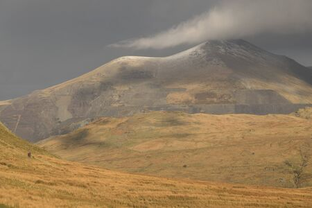 A cloud touches the snow dusted peak of Elidir Fawr on a sunny day in the Snowdonia National Park, Gwynedd, Wales, UK