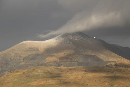 A view of the south flank of Elidir Fawr with a cloud touching the peak and a red and white rescue helicopter under the cloud in the Snowdonia National Park, Gwynedd, Wales, UK.
