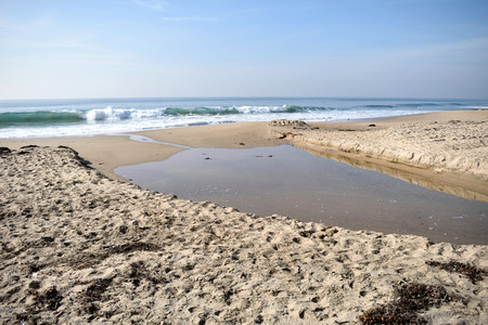 Waves rolling in from the Pacific Ocean approach a tidal pool at Crystal Cove Beach in California.