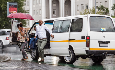 People getting out of taxi in city center. Johannesburg, South Africa -February 15, 2018. 報道画像