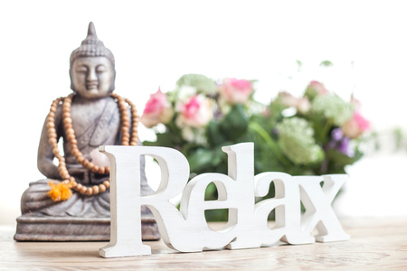 Buddha statue with beads. Buddha statue and the word relax in wood lettering. Stock Photo