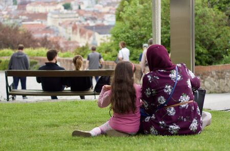Muslim family is sitting in the meadow Stock Photo